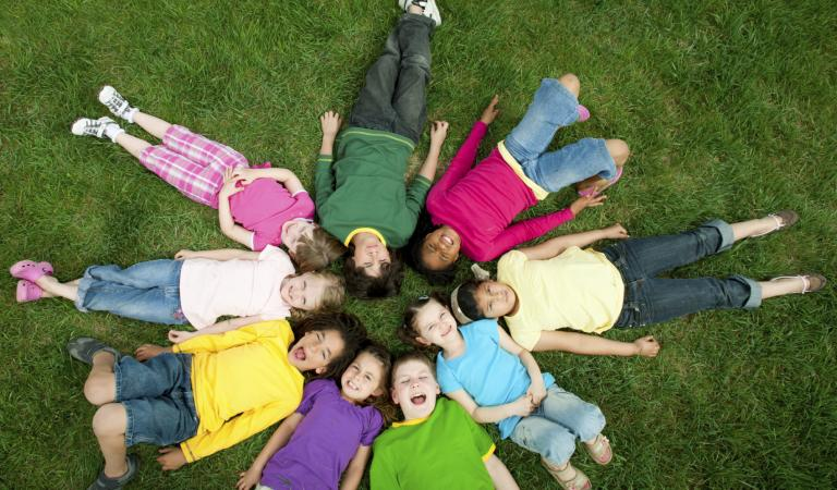 Diverse children outside on the grass having fun. Photo: iStockphoto