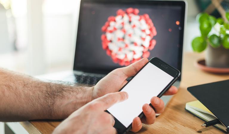 Homem usando smartphone com tela branca para texto em uma mesa de madeira em hom