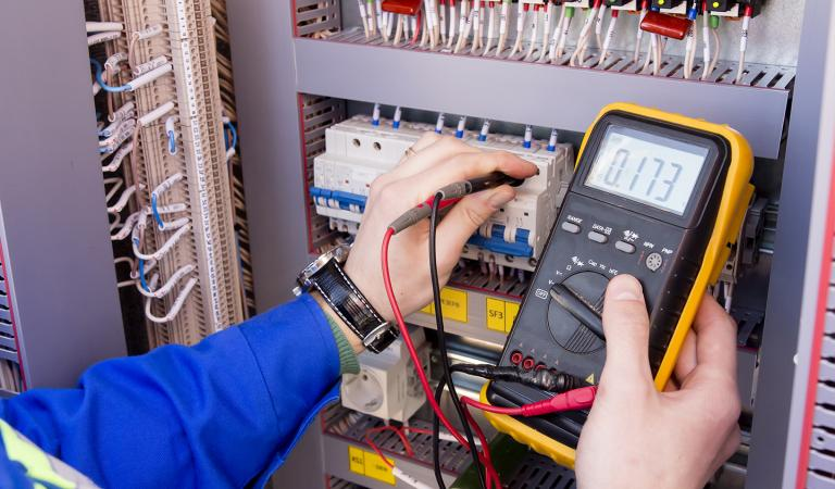Multimeter is in hands of engineer in electrical cabinet