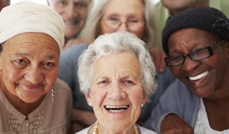 Um grupo de idosos sorrindo juntos em uma casa de repouso