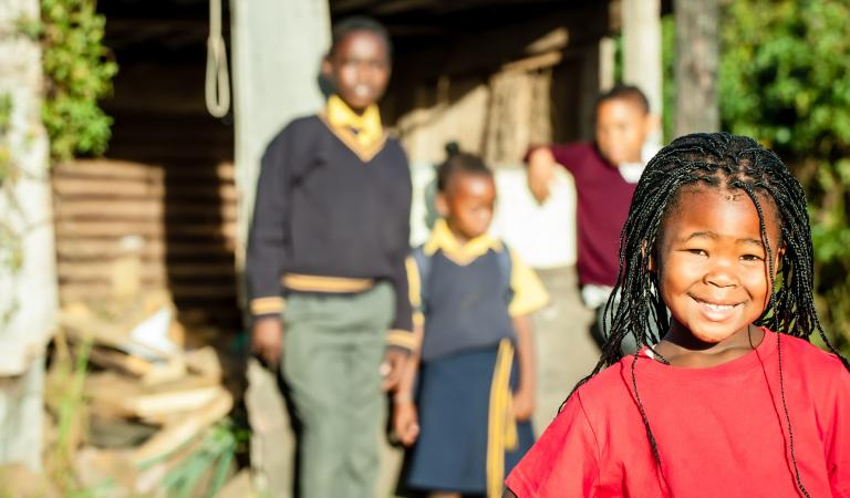 A pretty african girl with braided hair and a bright red shirt smiling confidently with her siblings in the backround watching over her. Photo: Nolte Lourens - stock.adobe.com