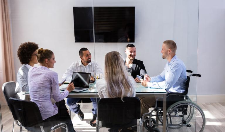 Disabled male manager sitting with his colleagues at workplace. Photo: iStockphoto
