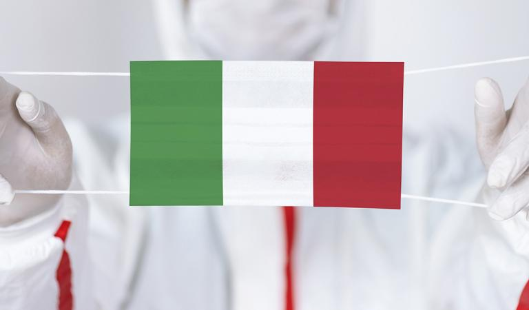 Healthcare personnel is holding Italian Flag shaped surgical mask