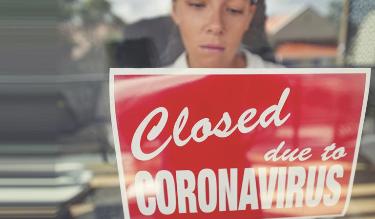 Store owner putting up a closed sign in the window. Sign says: closed due to coronavirus