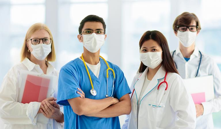 Mixed race Asian and Caucasian doctor and nurse meeting. Clinic personnel wearing face mask and stethoscope.