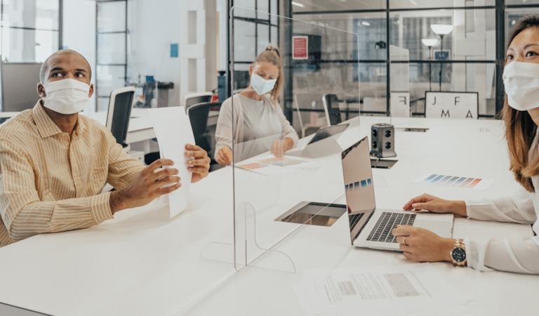 Empresários trabalhando no escritório com divisória de vidro dividindo-os
