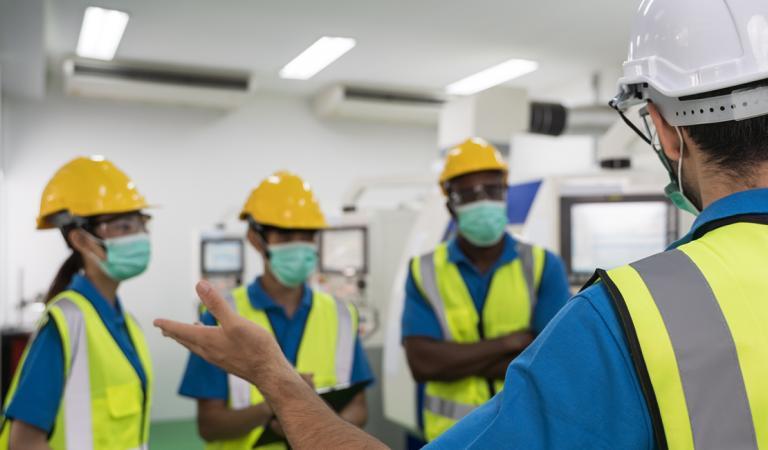 Trabalhadores da fábrica se reunindo antes do trabalho e colocam uma máscara