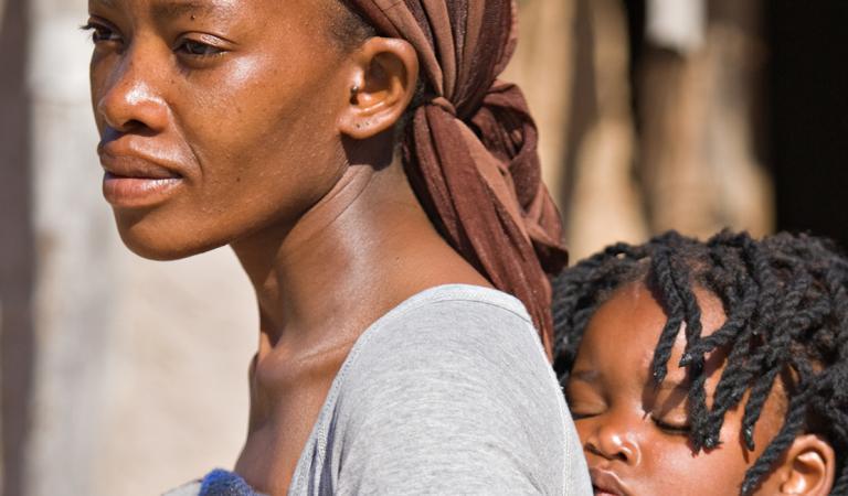 Mãe africana carregando o filho de maneira tradicional na frente da cabana