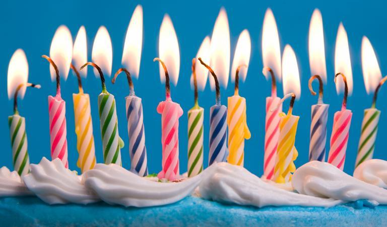 Close de velas de aniversário em chamas em um bolo contra um fundo azul