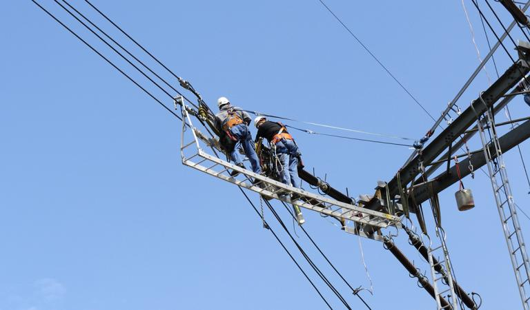 Two electricians working high above on a electricity pylon. Photo: iStockphoto