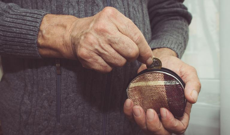 An elderly man puts a coin in an empty wallet. Photo: iStockphoto